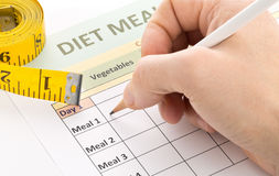 Dieting weight loss concept - man filling out diet planning form Stock Image