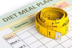 Dieting weight loss concept - measurement tape on meal planning Royalty Free Stock Photo