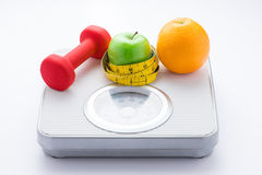 Dieting weight-loss slim down concept. Closeup measuring tape on white weight scale Royalty Free Stock Image