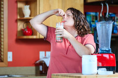 Dieting. A woman drinks bad tasting diet shake while pinching her nose Royalty Free Stock Photos