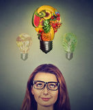 Dieting woman. Girl in glasses thinking looking up at food light bulbs Stock Photos