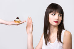 Dieting woman refusing cake. Young resolute dieting beautiful woman refusing tart cake with cream and chocolate, studio, healthy lifestyle concept, gray royalty free stock photos