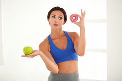Dieting young lady choosing food for fitness Stock Photos