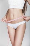 Dieting. Young woman measuring waist Royalty Free Stock Image