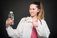 Dietista femminile che indica bottiglia di acqua e di sorridere Fotografia Stock Libera da Diritti