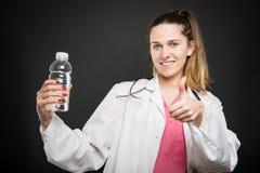 Dietista femminile che indica bottiglia di acqua che mostra come Fotografie Stock Libere da Diritti