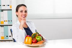 Dietista femminile che mostra le verdure e frutta fotografie stock libere da diritti