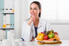 Dietista femminile che mostra le verdure e frutta fotografia stock libera da diritti