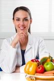 Dietista femminile che mostra le verdure e frutta fotografia stock