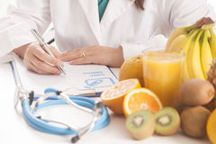 Dietitian doctor. With prescription and fruits Royalty Free Stock Image