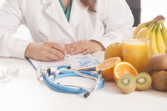 Dietitian doctor. Sittin on a desk Stock Images