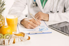 Dietitian doctor. Sittin on a desk Royalty Free Stock Images