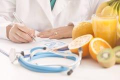 Dietitian doctor. Sittin on a desk Royalty Free Stock Photos