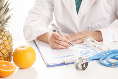 Dietitian doctor. Sittin on a desk Royalty Free Stock Photography