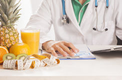 Dietitian doctor. Sitting on a desk Royalty Free Stock Photography