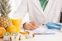 Dietitian doctor. Writing a prescription Royalty Free Stock Photos
