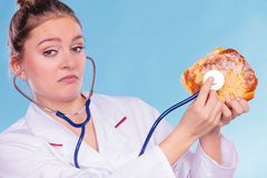 Dietitian examine sweet roll bun with stethoscope. Royalty Free Stock Photography