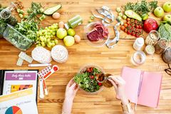 Dietitian making a salad on the tabe full of healthy ingredients royalty free stock photography