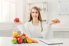 Dietitian nutritionist with bun and apple. Dietitian with bun and fresh apple. Woman nutritionist holding fruit and croissant comparing junk and healthy food Royalty Free Stock Photos