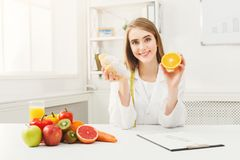 Dietitian nutritionist with bun and orange. Dietitian with bun and fresh orange. Woman nutritionist holding fruit and croissant comparing junk and healthy food Royalty Free Stock Photography