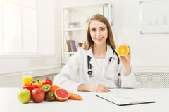 Dietitian nutritionist with fresh orange. Dietitian holding fresh orange. Woman nutritionist holding fruit. Right eating nutrition, healthy food, slimming, diet Stock Image