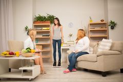 Healthy lifestyle explanation. Dietitian and overweight women looking at slim women tanding on scales royalty free stock images