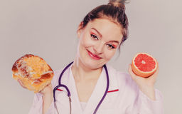 Dietitian with sweet roll bun and grapefruit. Stock Images