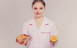 Dietitian with sweet roll bun and grapefruit. Royalty Free Stock Photography