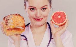 Dietitian with sweet roll bun and grapefruit. Royalty Free Stock Photo