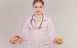 Dietitian with sweet roll bun and grapefruit. Stock Image