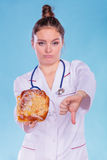 Dietitian with sweet roll bun. Unhealthy junk food Royalty Free Stock Photos