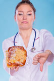 Dietitian with sweet roll bun. Unhealthy junk food Royalty Free Stock Image