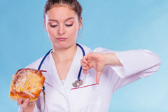 Dietitian with sweet roll bun. Unhealthy junk food Stock Photos