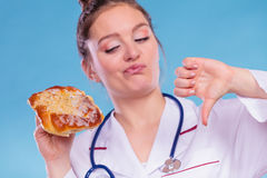 Dietitian with sweet roll bun. Unhealthy junk food. Dietitian nutritionist holding sweet roll bun showing thumb down gesture. Woman with fattening junk food. Bad Royalty Free Stock Image