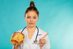 Dietitian with sweet roll bun. Unhealthy junk food Stock Images
