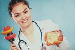 Dietitian with sweet roll bun and vegetables. Royalty Free Stock Photography