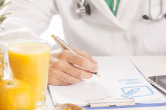 Dietitian. In uniform with stethoscope writing a diet form Royalty Free Stock Image