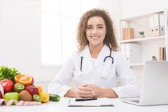 Dietitian working on diet plan at office, smiling at camera. royalty free stock photography