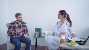 Dietology,有胡子的可爱的客户男性与关于减肥和健康营养开会的医生营养师协商 股票视频