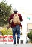 Dietro del giovane che cammina all'aperto con la borsa ed il pattino Immagine Stock