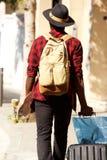 Dietro dell'uomo che viaggia con i bagagli ed il pattino Fotografia Stock