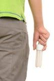 Dietro la mano tiene di potenza di risparmio la lampada in su Immagine Stock Libera da Diritti