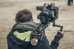 Dietro la scena Scena del film della fucilazione del cineoperatore con la sua macchina fotografica immagini stock libere da diritti