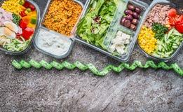 Diety jedzenie i lunchów pudełek pojęcie Różnorodne Zdrowe warzywo sałatki w plastikowych pakunkach z pomiar taśmą, odgórny widok Fotografia Stock