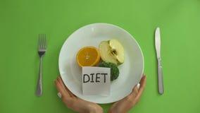 Diety notatka na talerzu z owoc i warzywo, ręki wiązał z pomiarową taśmą zdjęcie wideo