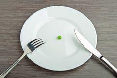Diety pojęcie. na biel pustym talerzu jeden groch Fotografia Stock