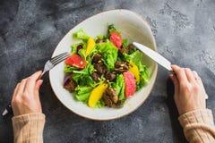 Diety sałatka z cytrusem, sałatą i piec na grillu kurczak wątróbką w, kobiecej ręce i talerzu Obrazy Royalty Free