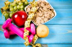 Diety sprawności fizycznej pojęcie dumbbells, pomiarowa taśma, płatki i świeże owoc na drewnianym stole -, Obraz Royalty Free