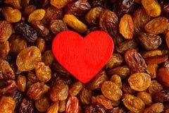 Diety zdrowy jedzenie. Rodzynka jako tło czerwieni i tekstury serce Fotografia Royalty Free