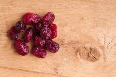 Diety zdrowy jedzenie. Rozsypisko wysuszeni cranberries na drewnianym tle Obraz Stock